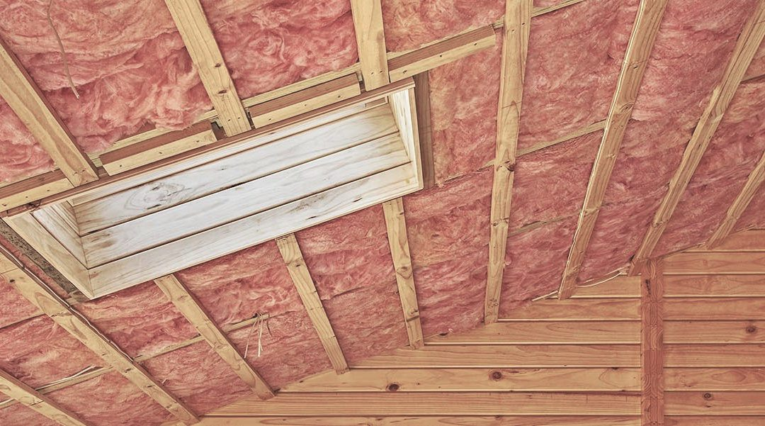 Fiberglass insulation installed in the sloping ceiling of a timber house.